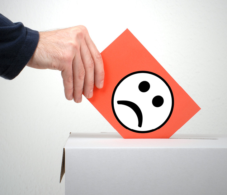 hand putting a card with a smiley face icon with downturned mouth into a complaint box