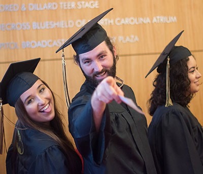 male and female students in commencement regalia making funny faces and pointing at camera