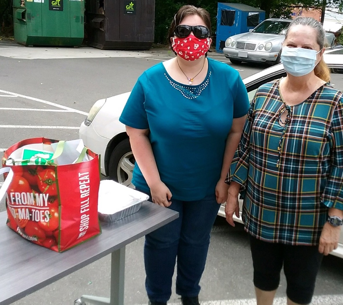 two students with face masks standing next to their bag of groceries