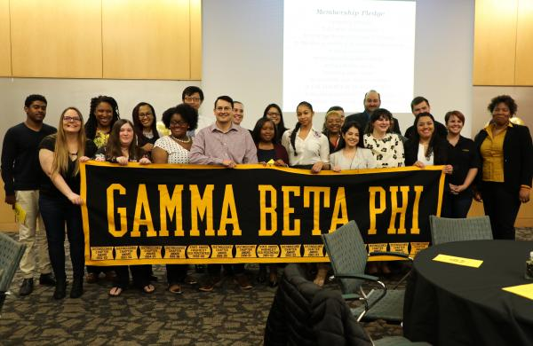 group photo of students holding sign that says gamma beta phi