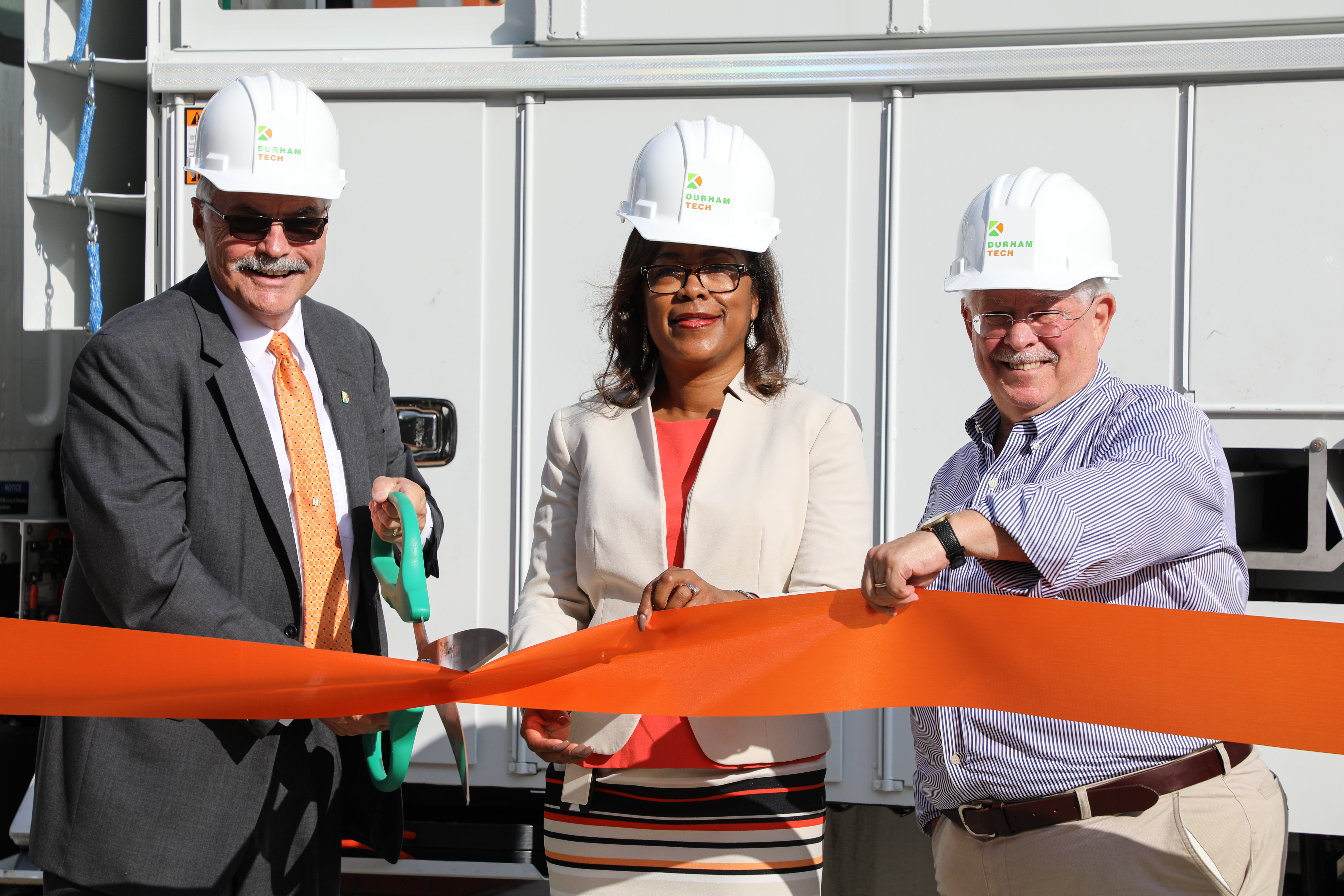 Durham Tech President Bill Ingram, Duke Energy District Manager Indira Everett, and Durham Tech Board of Trustees Chairman John Burness cut a ribbon in celebration of the new Electrical Line Technician Program at Durham Tech.