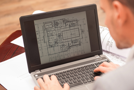 A photo of a generic student looking at an architectural design on a laptop.