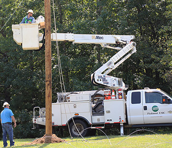 electrical line worker being lifted in bucket of a truck to fix wiring on phone pole