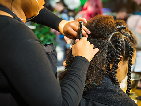 Hair stylist braiding another woman's hair