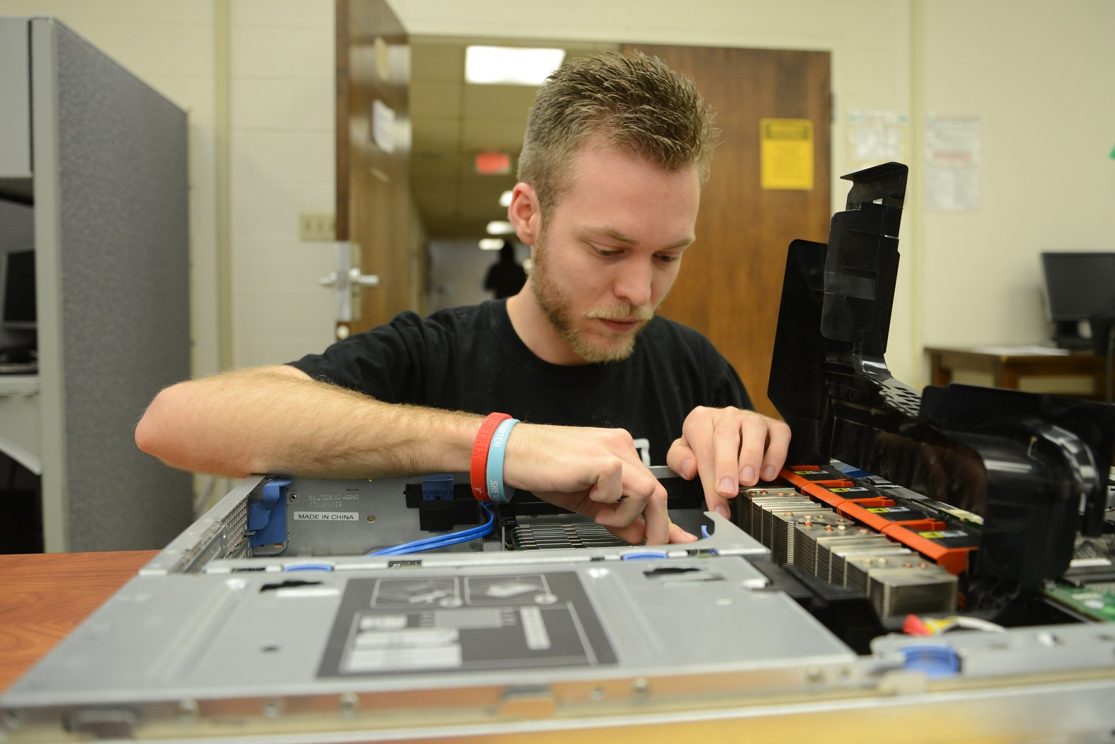 student working on large piece of computer equipment, looking down at it