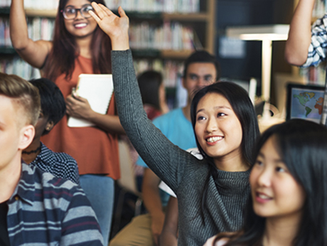 Diverse group of students raising their hand in a class