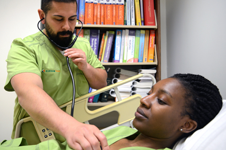 A male student wearing medical scrubs practices using a stethoscope on a female student while she lays on a gurney.