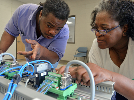 male student and female student observe controller in advanced manufacturing class