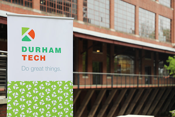 Brick Warehouse building with a Durham Tech banner in front saying Do Great Things