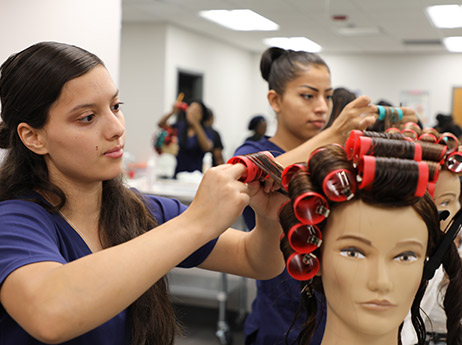 Students practice roller sets on dummy heads