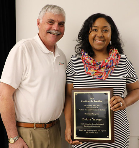 Diedre holds her award proudly while posing with President Ingram