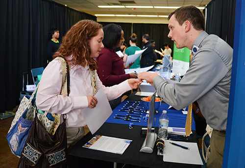 student speaks with a recruiter at a career fair