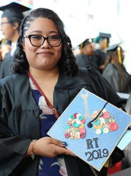 Dulce Hernandez holds up a sparkling bright blue mortarboard at graduation with RT 2019 printed on it