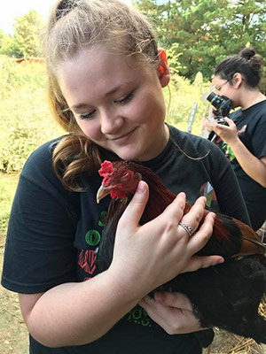 student holding a chicken in her arms