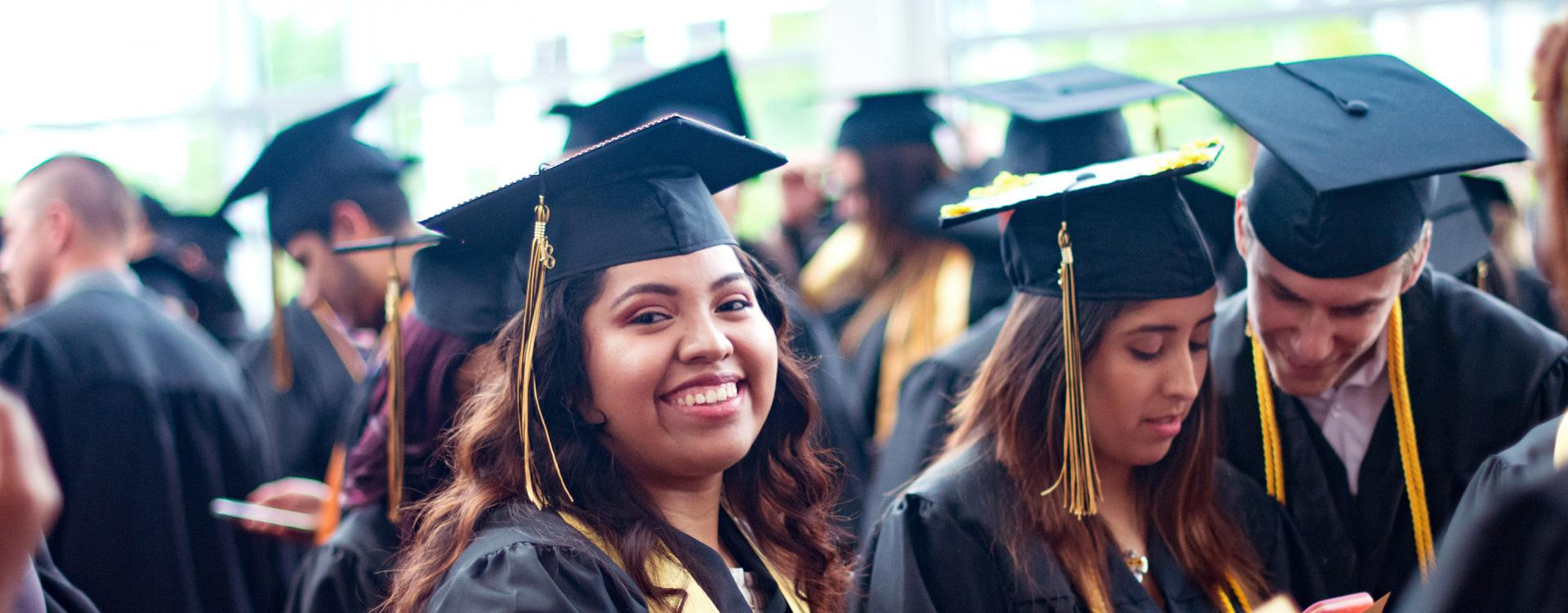 A Durham Tech student wearing a cap and gown smiles during commencement.