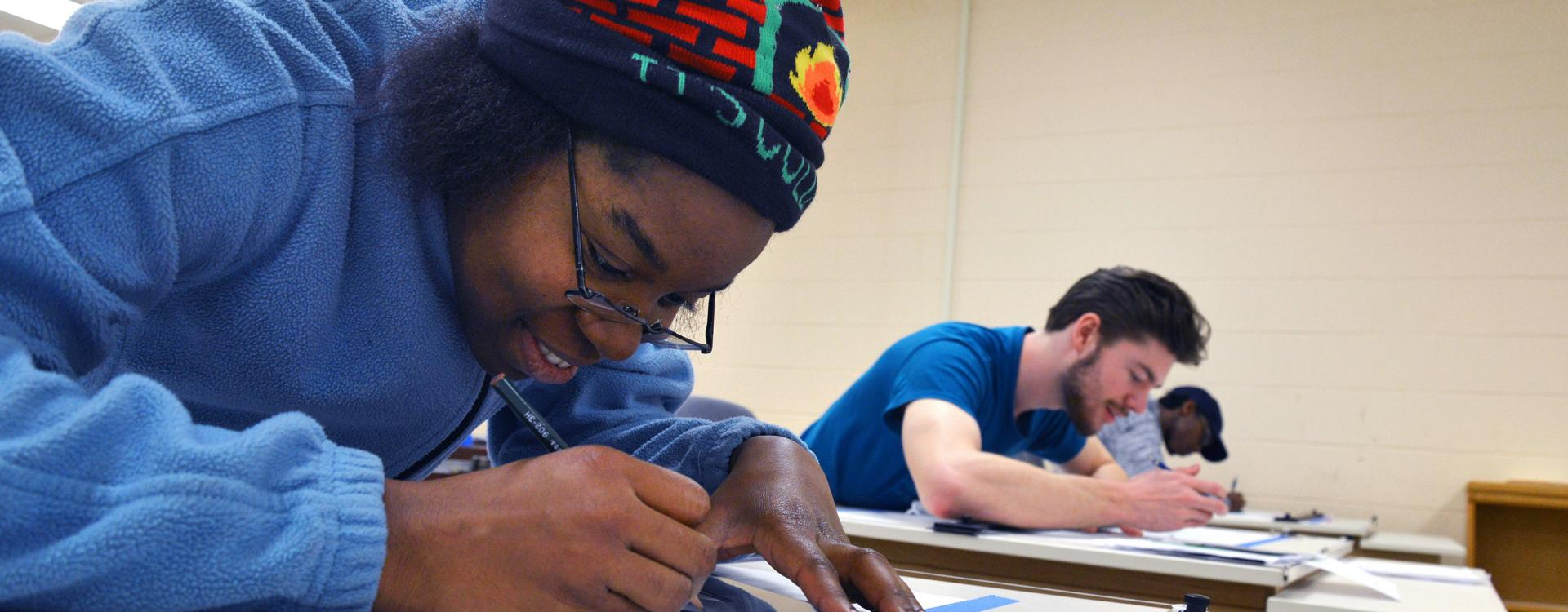 A Durham Tech student holds a pencil and focuses on work in a classroom