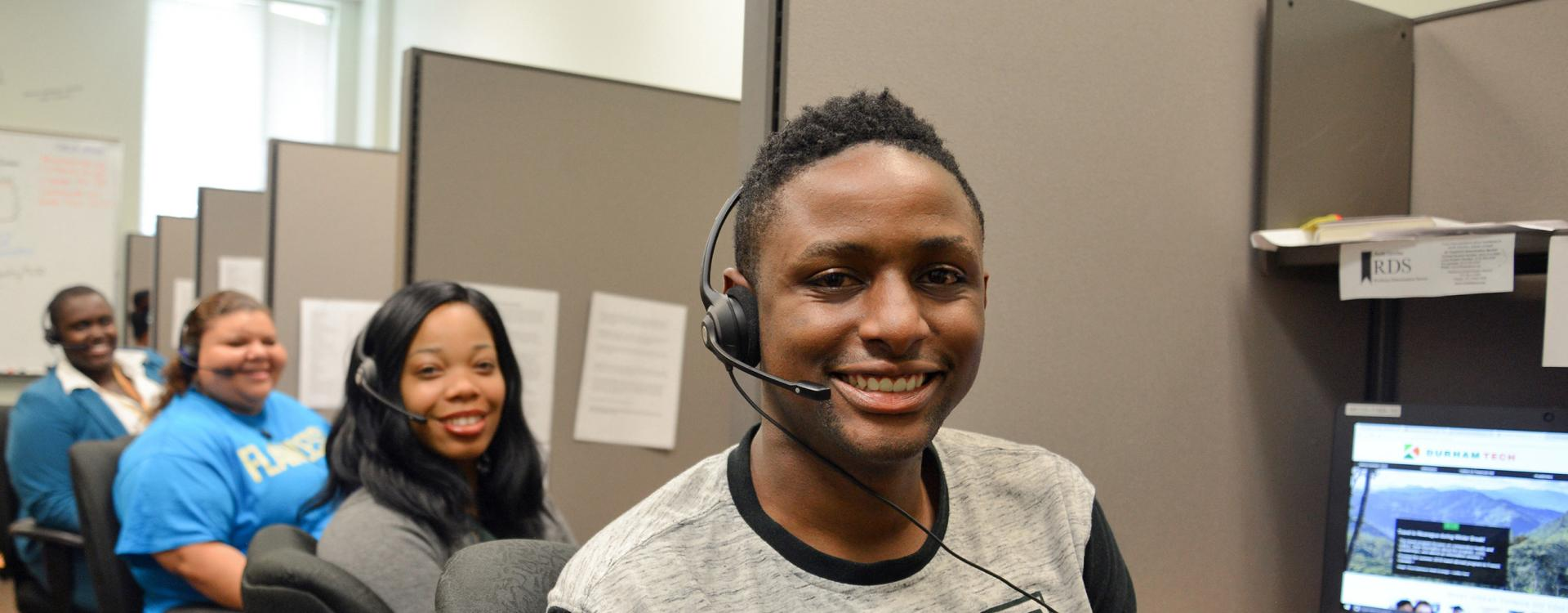 Student Communication Assistants facing camera wearing headphones to answer calls