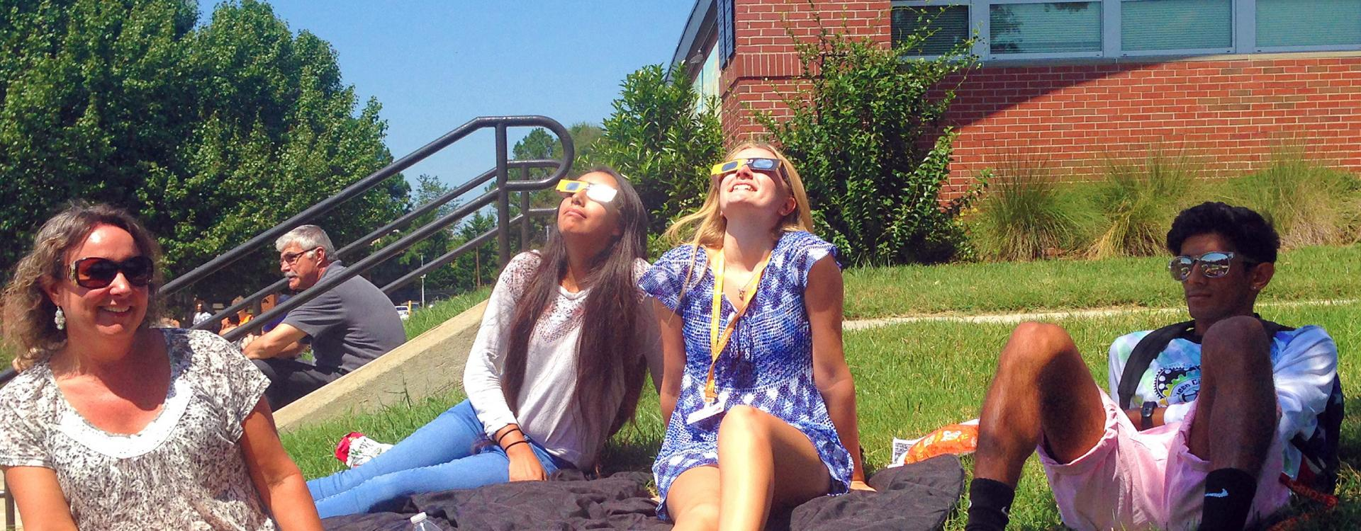 students wearing protective glasses sit on campus watching solar eclipse
