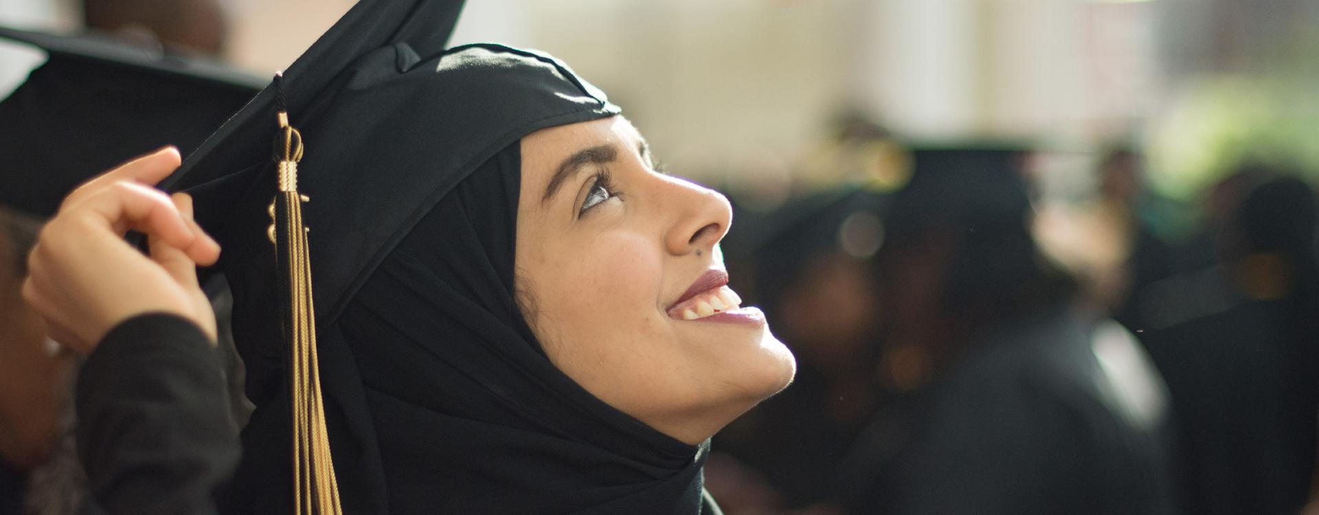 female student in graduation regalia looks up smiling
