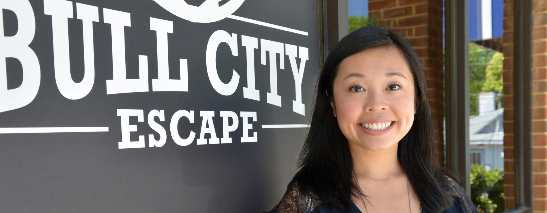 female business owner stands in front of Bull City Escape sign