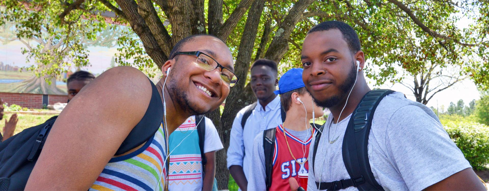 two students on main campus plaza outside smiling at camera