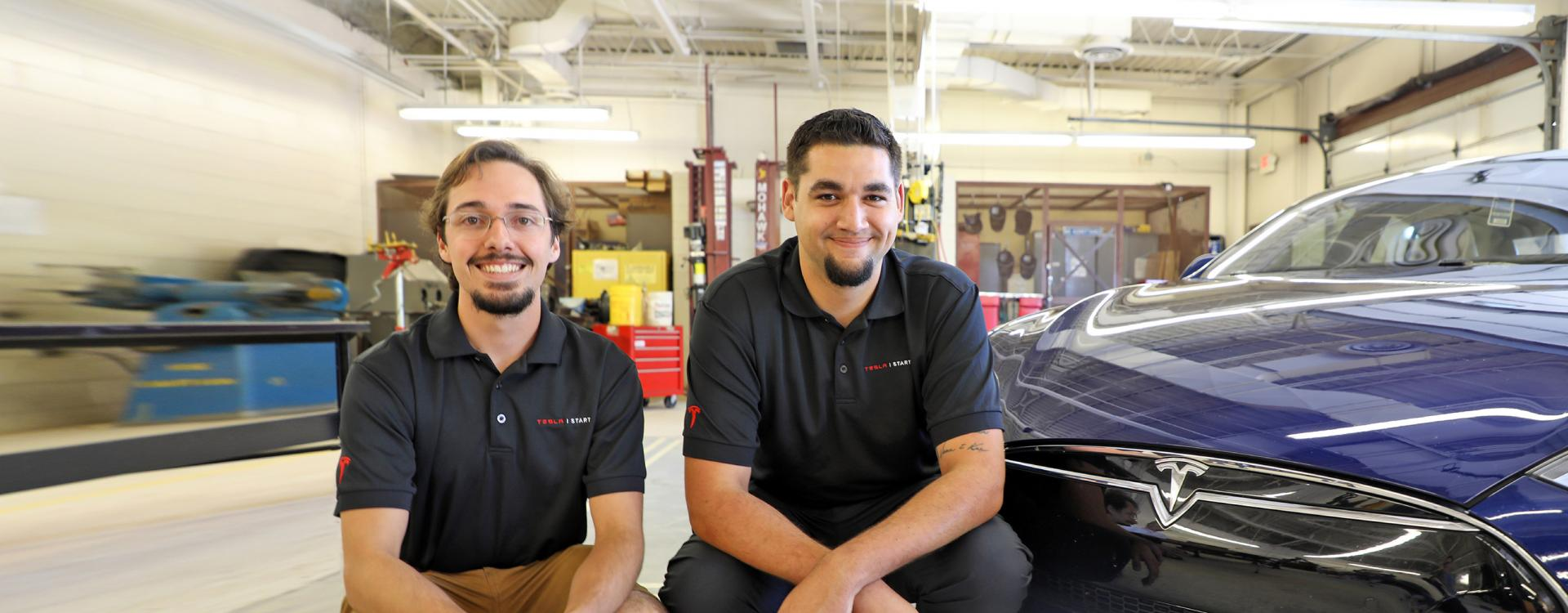 two automotive students on internship sitting next to Tesla car