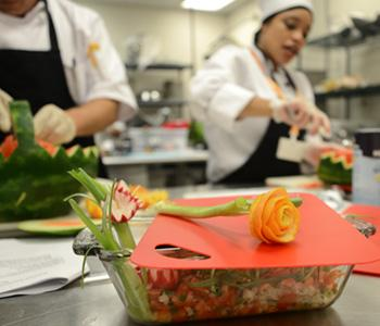 Rose made from carrot shavings with culinary students in background artfully carving watermelons