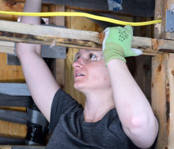 A female student in a construction trades course uses her left hand to steady herself as she looks upward into the rafters of a structure.