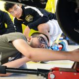 Photo of male student working under car with two students looking on in automotive class.