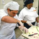 male and students use chef's knife to cut scallions