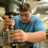machining student works on milling machine, leaning over looking closely and wearing goggles