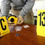 Evidence markers sit on a desk as a Criminal Justice Technology student measures the distance between areas of a training crime scene.