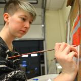 A student in the Associate in Fine Arts program at Durham Tech paints with her right hand.